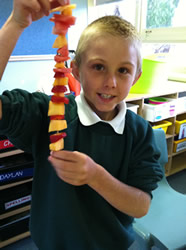 Student smiling and holding up a fruit kebab he has made