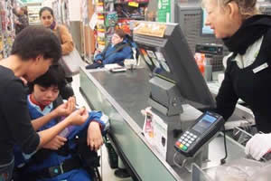 Teacher and student counting money at a supermarket cash register